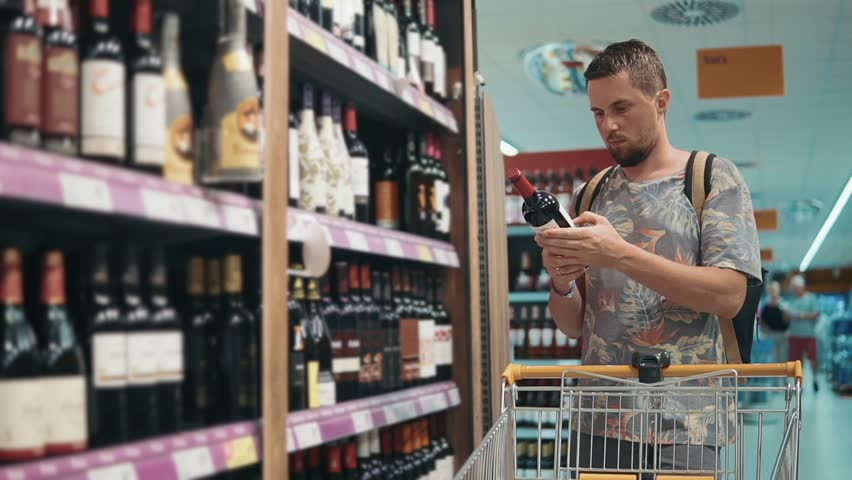 Grown Man With Backpack Choosing Bottle Of Wine On A Shelf In A Liquor Store Man Buying Alcohol Drinking Wine Red Wine