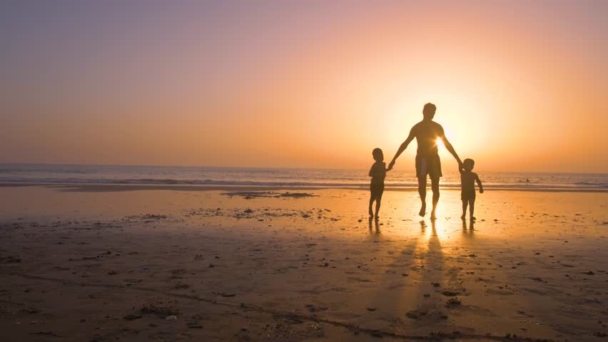 Silhouette of father with two children in the beach at sunset