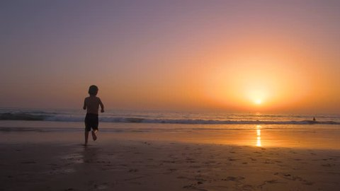 Silhouette of child running and playing  in the beach at sunset - freedom