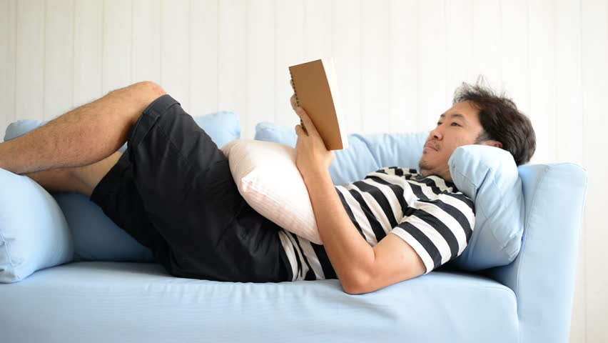 Asian man lying on blue sofa and reading book | Shutterstock HD Video #1018205920
