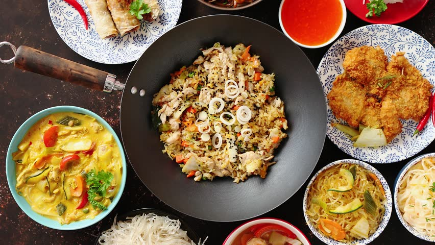 Asian oriental food composition in colorful dishware, served on dark rustic background, top view. Chinese, vietnamese, thai cuisine set. With copy space. Royalty-Free Stock Footage #1018208092