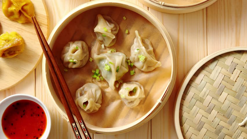 Traditional chinese dumplings served in the wooden bamboo steamer over raw wooden background table. Top View composition.