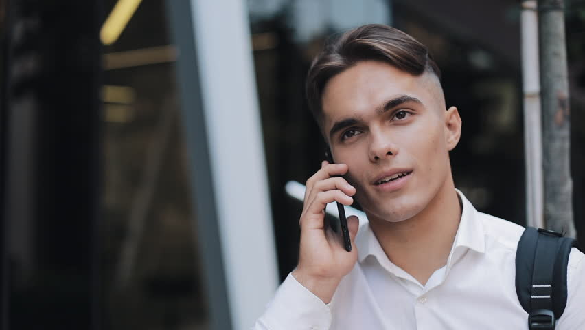 Happy ypung businessman with a backpack talking at phone. He standing near modern office building.Concept: technology, telephony, business trips, business | Shutterstock HD Video #1018211509