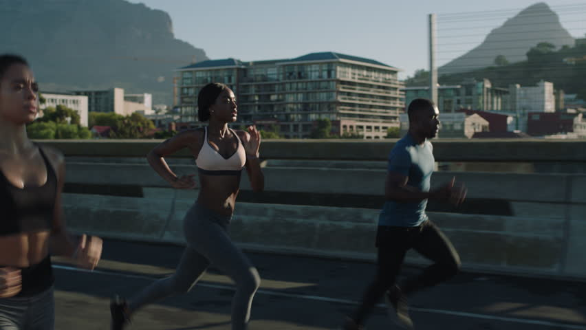 Multi ethnic group athletes running friends enjoying competition race jogging exercising together focused on healthy fitness lifestyle in urban city at sunrise | Shutterstock HD Video #1018213054