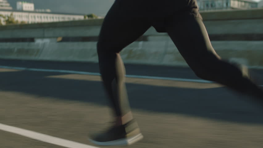 Close up athlete legs running on road fit runner jogging sprinting endurance exercise in urban city morning at sunrise | Shutterstock HD Video #1018213108