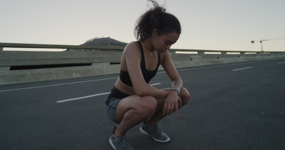 attractive hispanic woman runner resting exhausted after intense running workout training cardio athletic female sportswoman in city at sunrise close up #1018213927