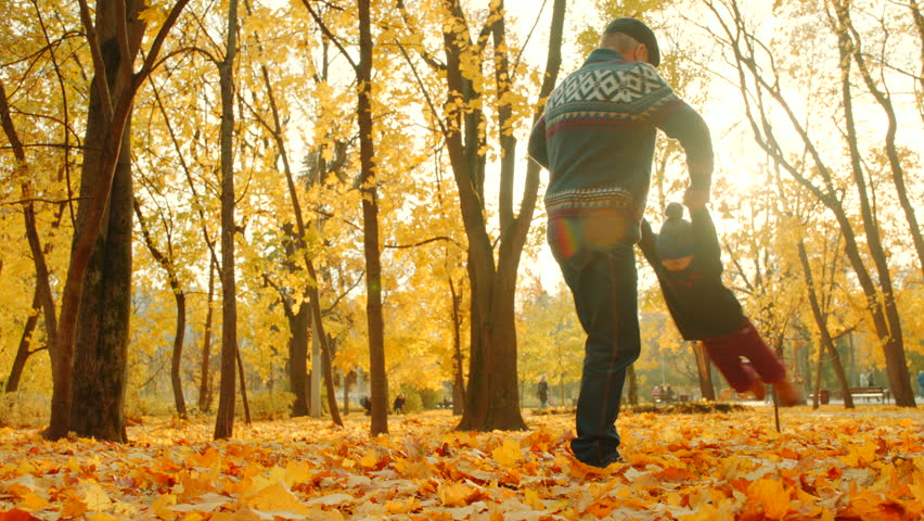 Grandfather playing with his grandson in the autumn park