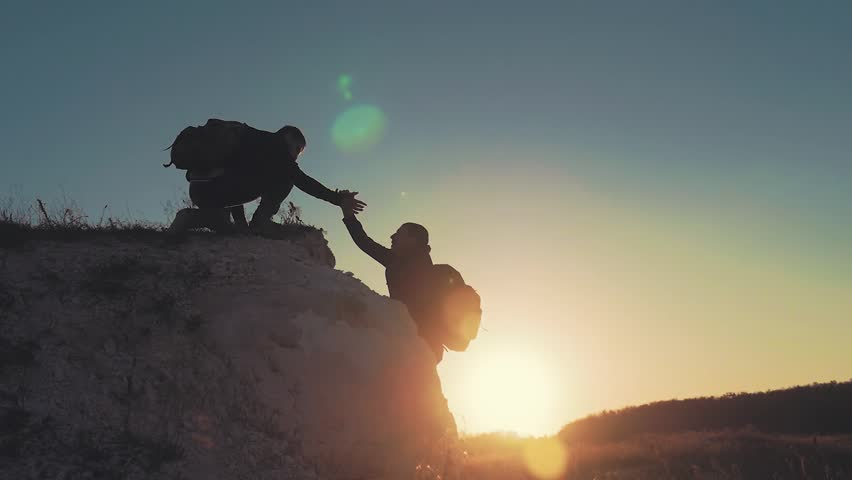 Climber helping teammate climb, the man with the backpack reached out a helping hand to his friend. Hiker helping friend while trekking on hill. Tourist man helps someone to climb the mountain. | Shutterstock HD Video #1018229182