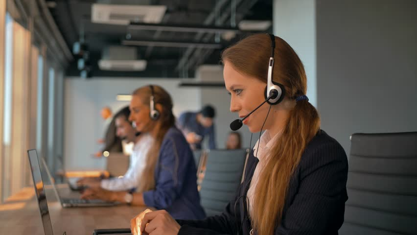 Female operator agent with headsets working in a call centre. They speaking about transaction and purchasing corporate plan of their big company. 4K UltraHD refocusing between people.