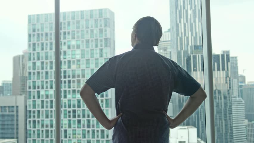 Young successful rich man comes to the window and admire the city center with skyscrapers view. 3840x2160 #1018237861