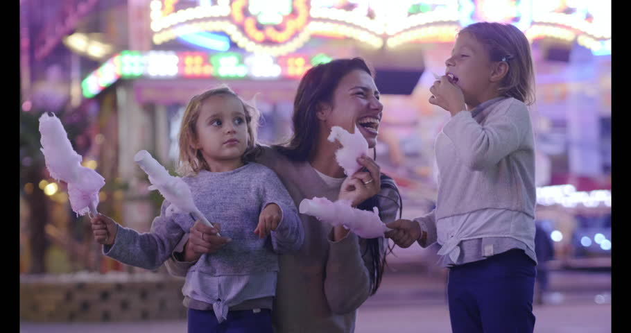 Portrait of a young mother having fun with her daughters at the Luna park. Concept: Family, happiness, freedom. Royalty-Free Stock Footage #1018241044