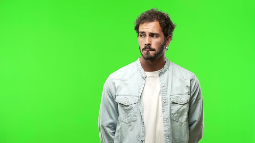 Young man on green chroma doubting and confused, thinking of an idea or worried about something