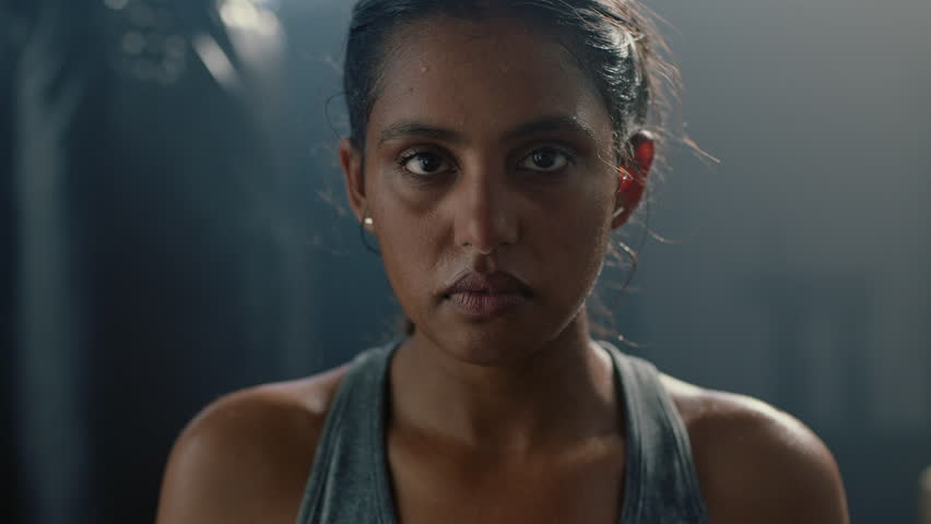 Portrait beautiful kickboxing woman fighter looking confident at camera tough female kickboxer fierce sportswoman sweating after training in fitness gym close up | Shutterstock HD Video #1018248094