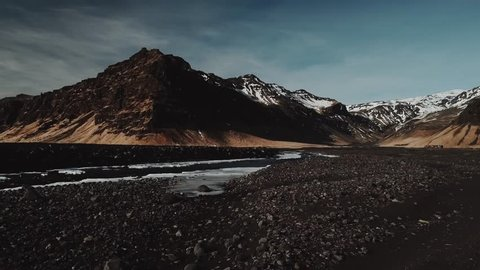 Water stream of mountain river in Iceland, is running between mountains covered in fresh snow. Late evening