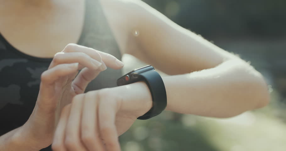 Young woman trying new smart watch. Smart watch. Woman Using Smart Watch and Smart Phone. Closeup
