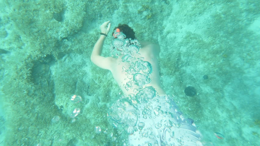 SLOW MOTION, GOPRO - A young man is snorkelling under the clear water - sea on a warm sunny day. He is making bubbles. #1018273996