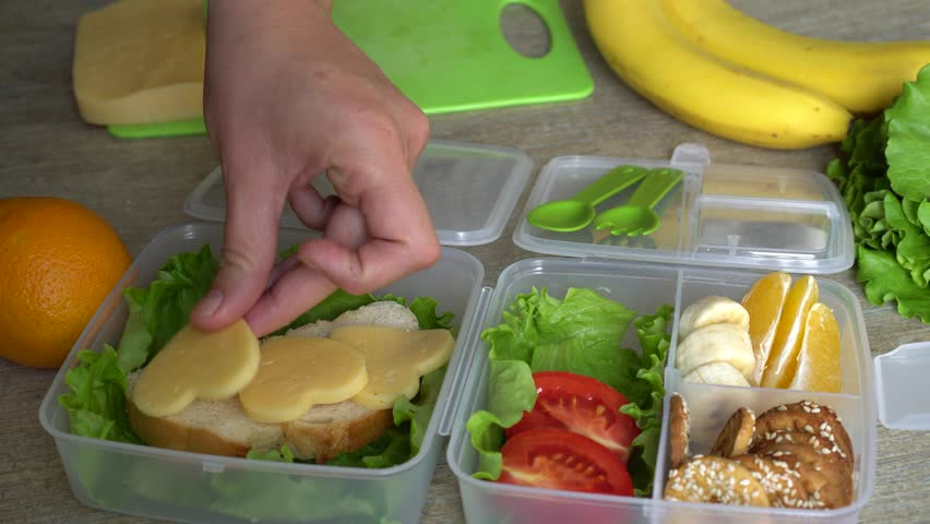Packing a Zero Waste Lunch. Mother putting food in lunch box. Packing healthy lunches for child care, preschool, kinder or school