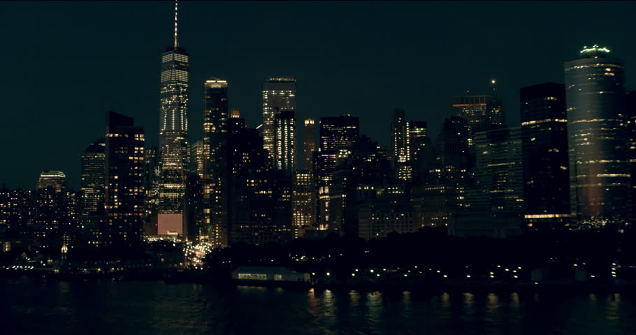 Aerial pan of downtown Manhattan skyscrapers and buildings, New York City, dark summer night light. Wide shot. 4k shot with a RED camera.