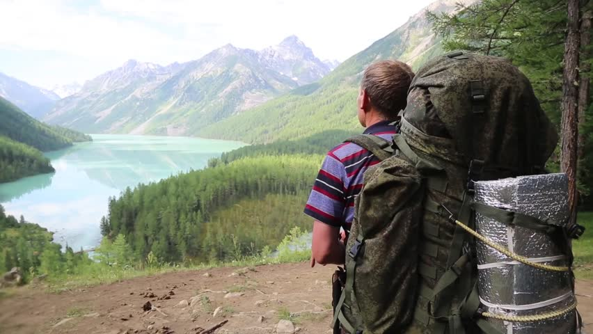 A tourist with a huge backpack looks at the lake. A man traveler stands on top of a mountain and looks into the distance on a clear lake. | Shutterstock HD Video #1018302856