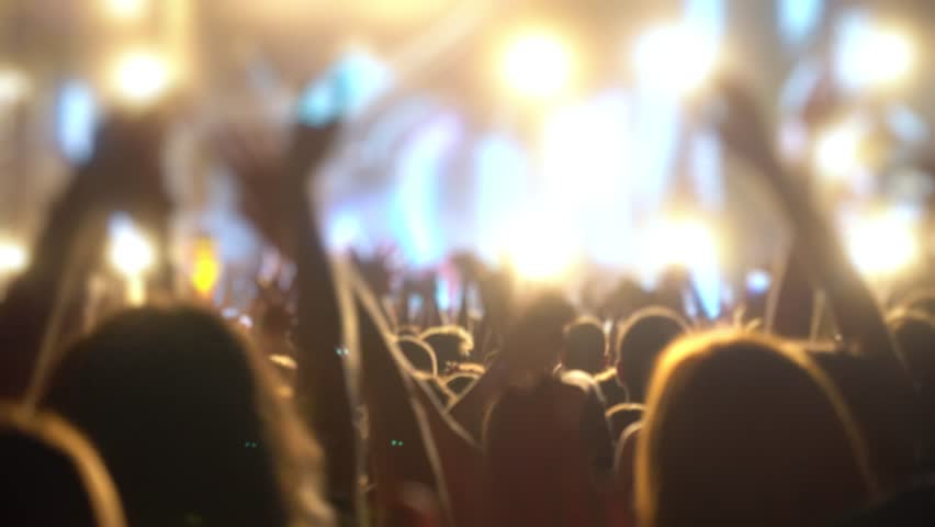 Happy people are watching an amazing musical concert. Merry fans jump and raise their hands up. Crowd of excited fans applauding to popular band performing favorite song. A group of fans with phones | Shutterstock HD Video #1018317007