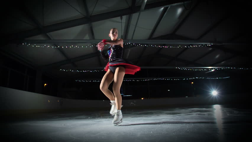 An elegant figure skater is having a beautiful performance in the ice rink.   Shutterstock HD Video #1018348387