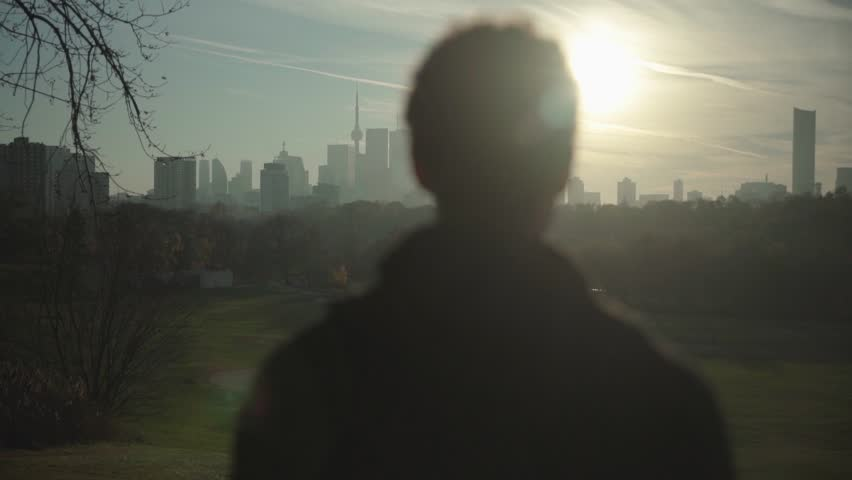 Young Adult Man Stands and Looks at City Skyline from a Distance, Silhouette of Millennial in a Park on Beautiful Sunny Evening at Golden Hour Before Sunset, Cinematic Slow Motion