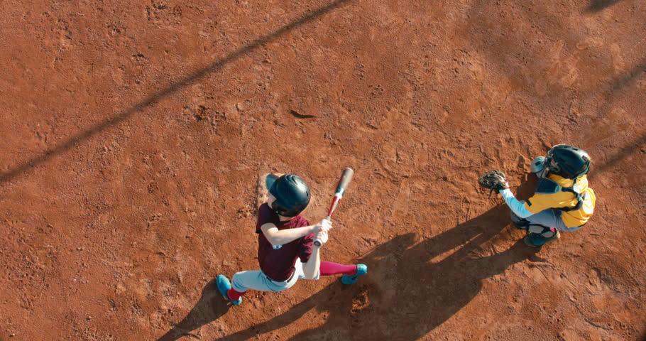 OVERHEAD CRANE Kid boy batter baseball player hits a ball over a home plate. 4K UHD 60 FPS SLO MO RAW