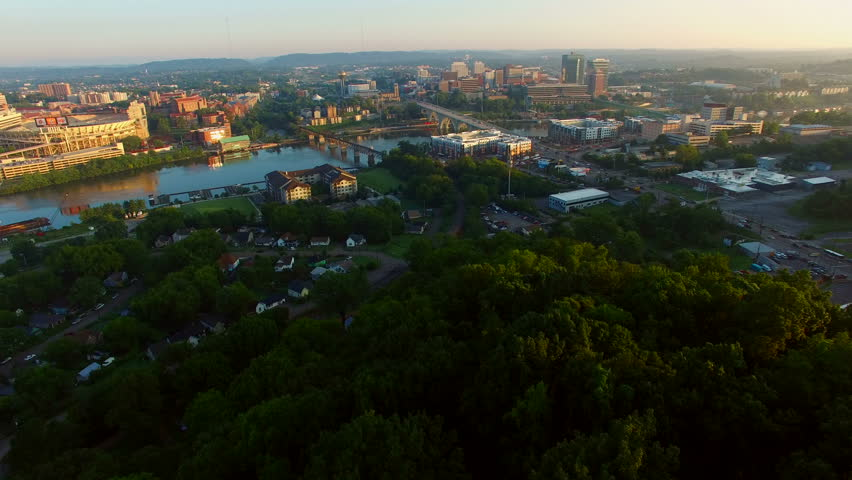 Slow reveal of the Knoxville skyline at sunrise over the trees of Fort Dickerson.