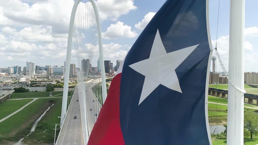 4K Texas Flag Slow Motion with Dallas Skyline In Background Aerial