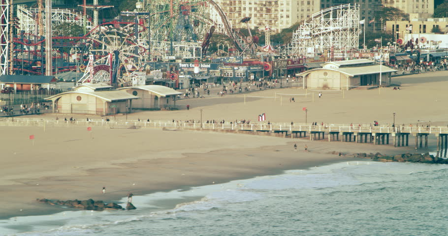 Coney Island, New York CIRCA - September 2018. Aerial pan of boardwalk, ferris wheel, and roller coasters at amusement park with bright day lighting.
