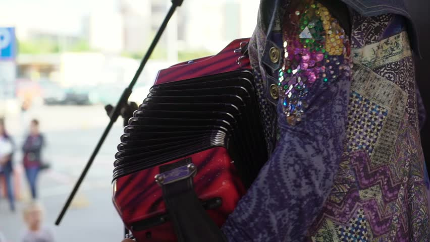 Close up musicians playing accordion on stage. Open air concert outdoors
