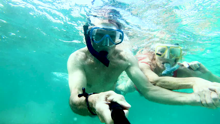 Selfie portrait of active senior Caucasian American couple snorkeling waving to camera making video diary and enjoying Summer adventure Bahamas USA