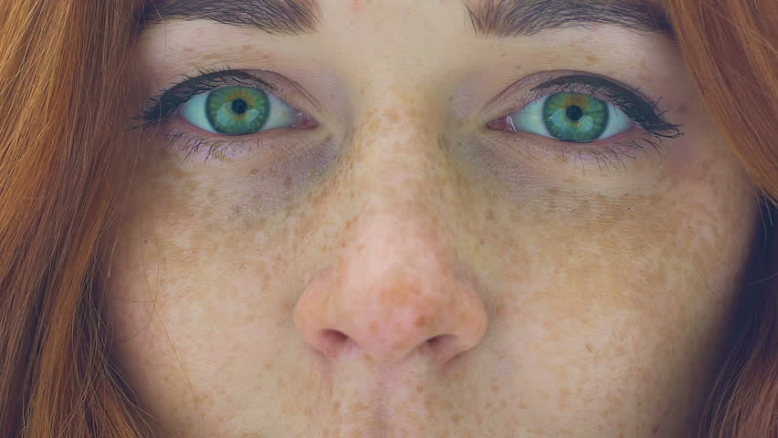Beautiful woman face with freckles red hair green eyes zoom in extreme close up