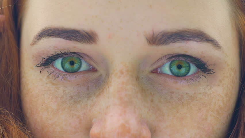 Freckled face of red haired woman with green eyes extreme close-up blink slow. Attractive adult female with eyelashes and lips natural make-up, looks into camera in slow-motion, perfect freckles.