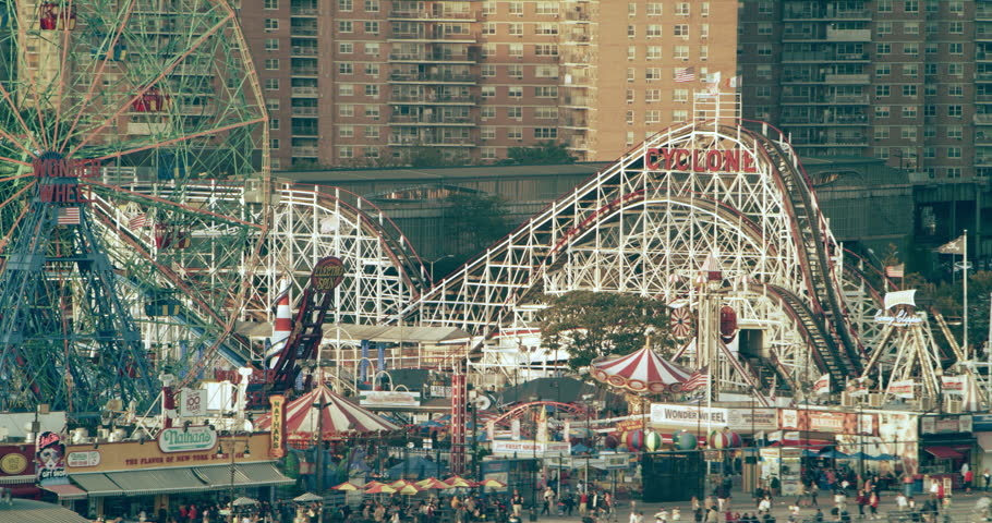 Coney Island, New York CIRCA - September 2018. Aerial view of roller coasters and ferris wheel at amusement park  New York City, bright day lighting. Close to Wide shot on 4k RED camera.