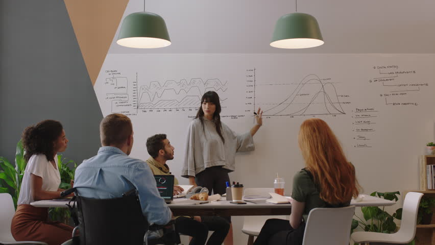 diverse business people meeting in boardroom brainstorming team leader woman presenting financial graph data showing colleagues presentation working together in disabled friendly office Royalty-Free Stock Footage #1018498531
