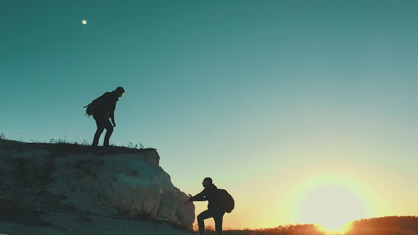 Silhouette of helping hand between two climber. two hikers on top of the mountain, a man helps a man to climb a sheer stone. couple hiking help each other silhouette in mountains with sunlight. | Shutterstock HD Video #1018518928