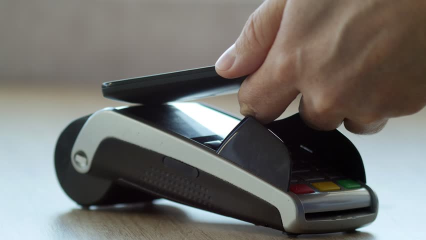 Customer paying with NFC technology by mobile phone on POS terminal in a shop | Shutterstock HD Video #1018531762