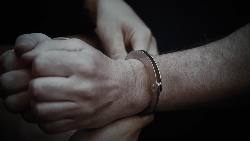 The men are handcuffed, they are caught by a gangster, the policemen are red-handed, they have taken a criminal, a close-up of the hands | Shutterstock HD Video #1018535038