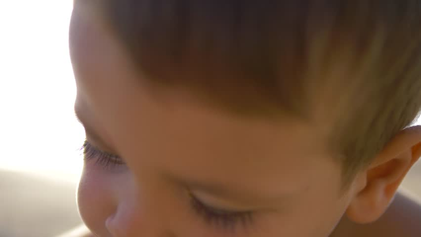 4K Slow motion - Caucasian Child with blue eyes looking at the camera in a sunny day #1018539064