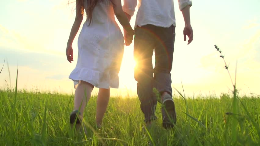 Happy Young Couple Walking on Summer field and smiling, holding hands walk through a wide field, having fun outdoors. Countryside. Man and woman on the meadow. Sun flare. Slow motion Full HD 1080p #10185455
