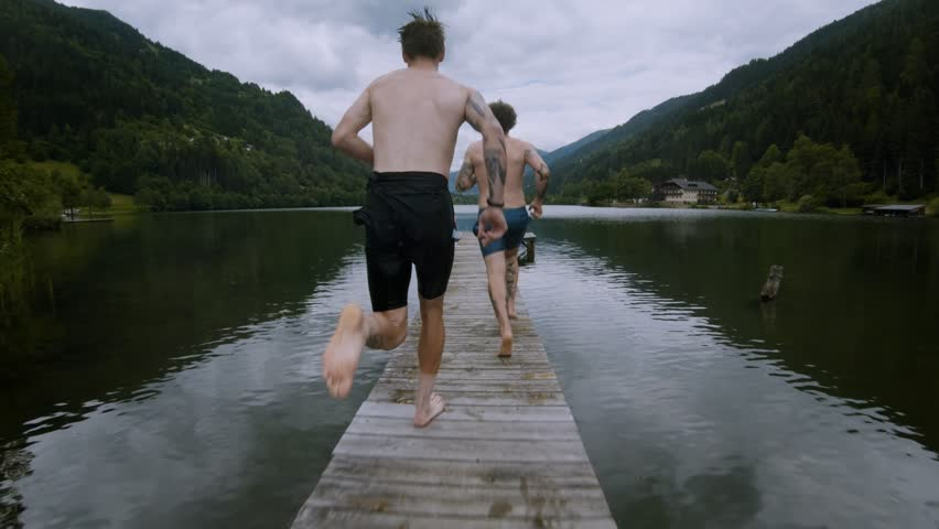 Two friends on summer vacation or holiday run on wooden boardwalk on alpine mountain lake, jump into cold fresh clean water to get refreshed in heat, natural outdoor lifestyle #1018564099