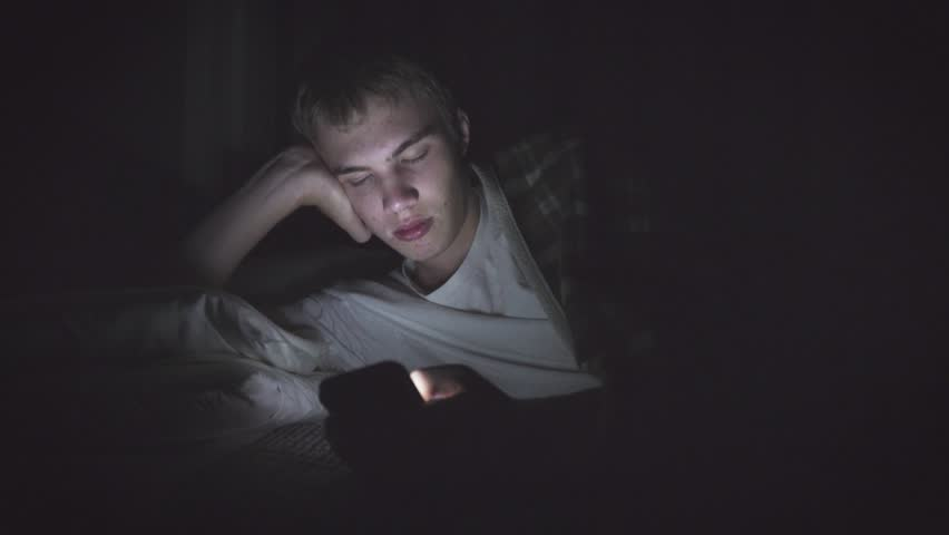 Bored teenager lying on his bed in the dark while scrolling through his phone. The light from the phone is illuminating his face. | Shutterstock HD Video #1018576621