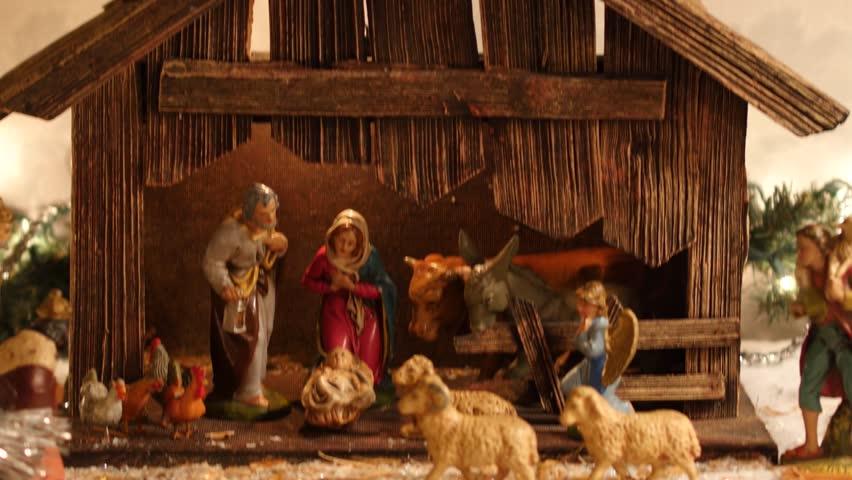 Tilt from the top to the bottom of a vintage old Christmas nativity or manger scene (creche) featuring animals, angels, a shepherd, magi and the holy family (Mary, Joseph and Baby Jesus).