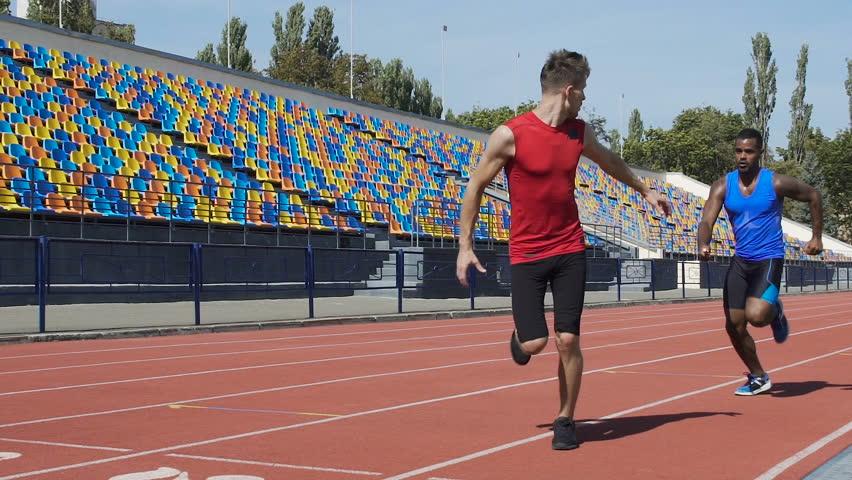 Athletes training relay race on empty stadium, teamwork, aspiration to win | Shutterstock HD Video #1018598485