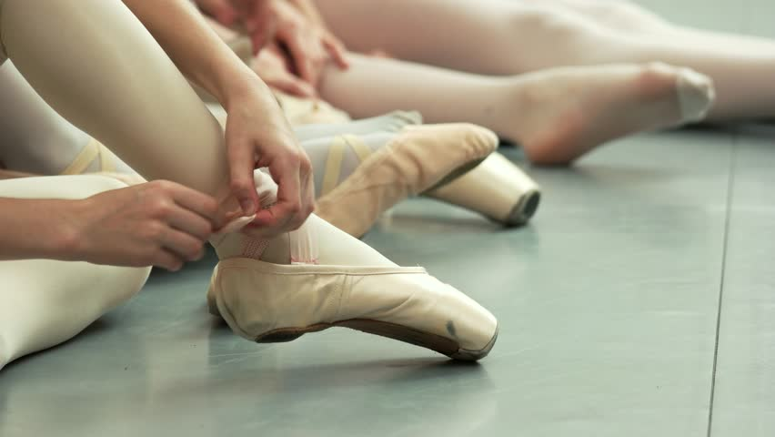 Group of young ballerinas taking off pointe shoes. Little caucasian ballet-dancer untie her ballet slippers. Ballet dance classes.