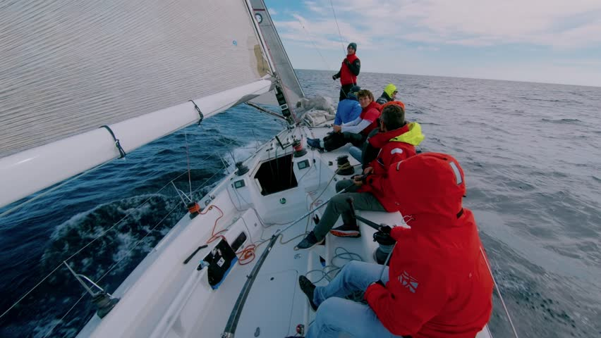 Group of men in red sailing outdoor jackets sit on deck of professional racing sailboat, sailors listen to captain give orders, sail in open waters of sea or ocean. Team work for common win or success