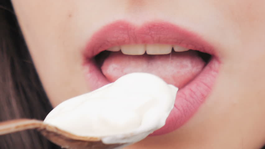 The girl with lipstick makeup eats yogurt from a spoon. Close up. | Shutterstock HD Video #1018608025