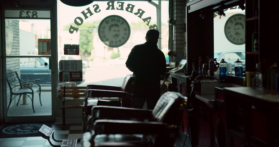 Trendy hair stylist getting shop ready for business in interior hipster barbershop with dim day lighting. Wide shot on 4k RED camera.