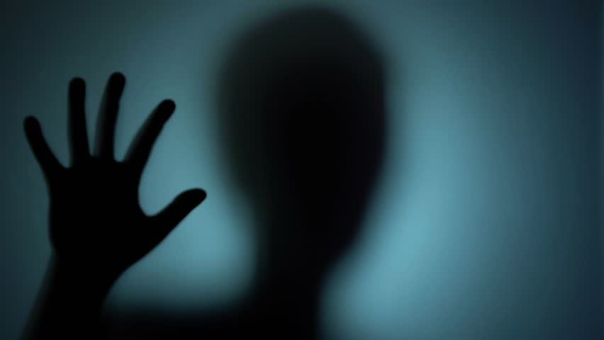 Mental hospital patient behind the glass, creepy silhouette, horror scene. Blood-chilling horror thriller shot | Shutterstock HD Video #1018622332